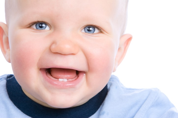 Cute baby looking into camera and laughing, showing two teeth